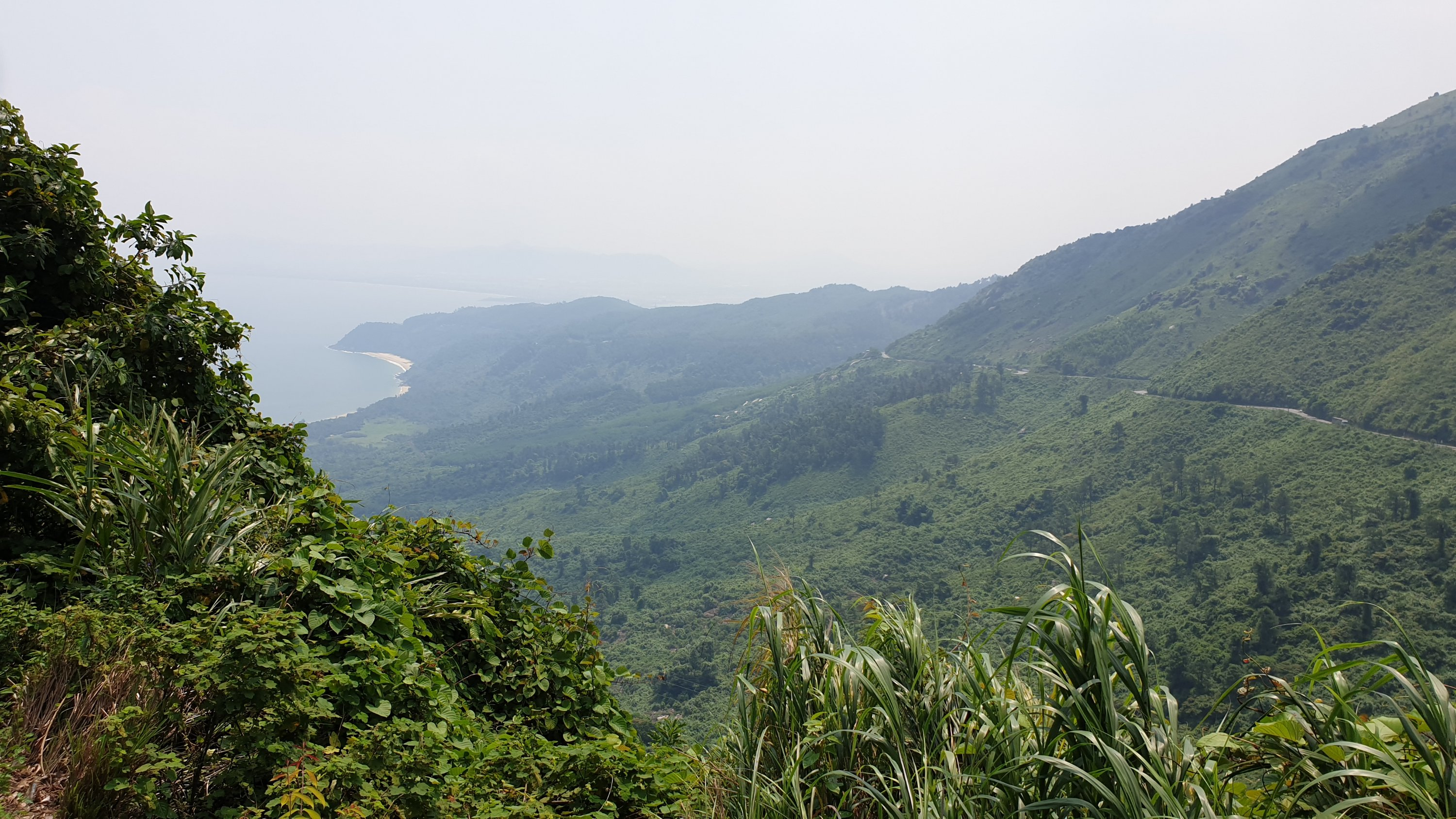Hai Van Pass view from the mountains down onto sloping hillsides and the sea
