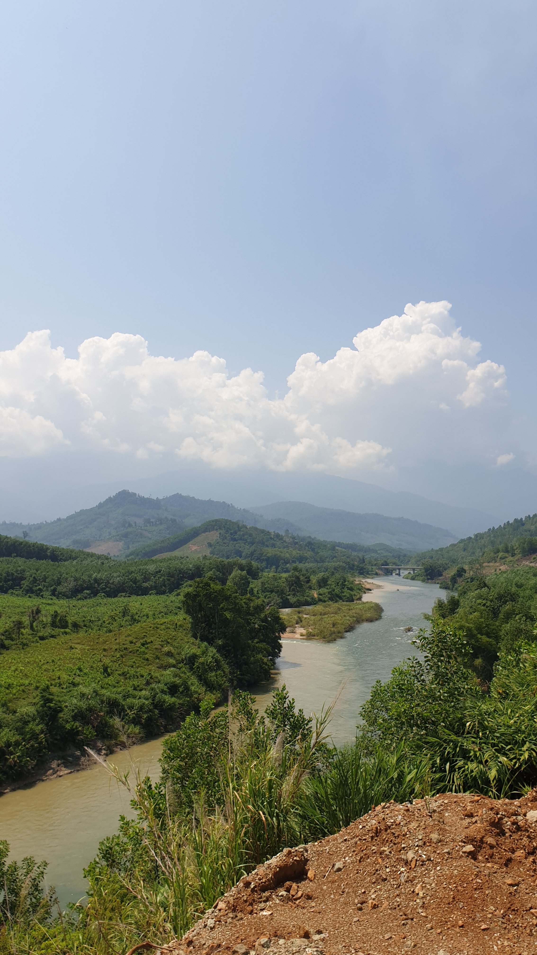 View of river valley in Vietnam with trees and mountains in the background