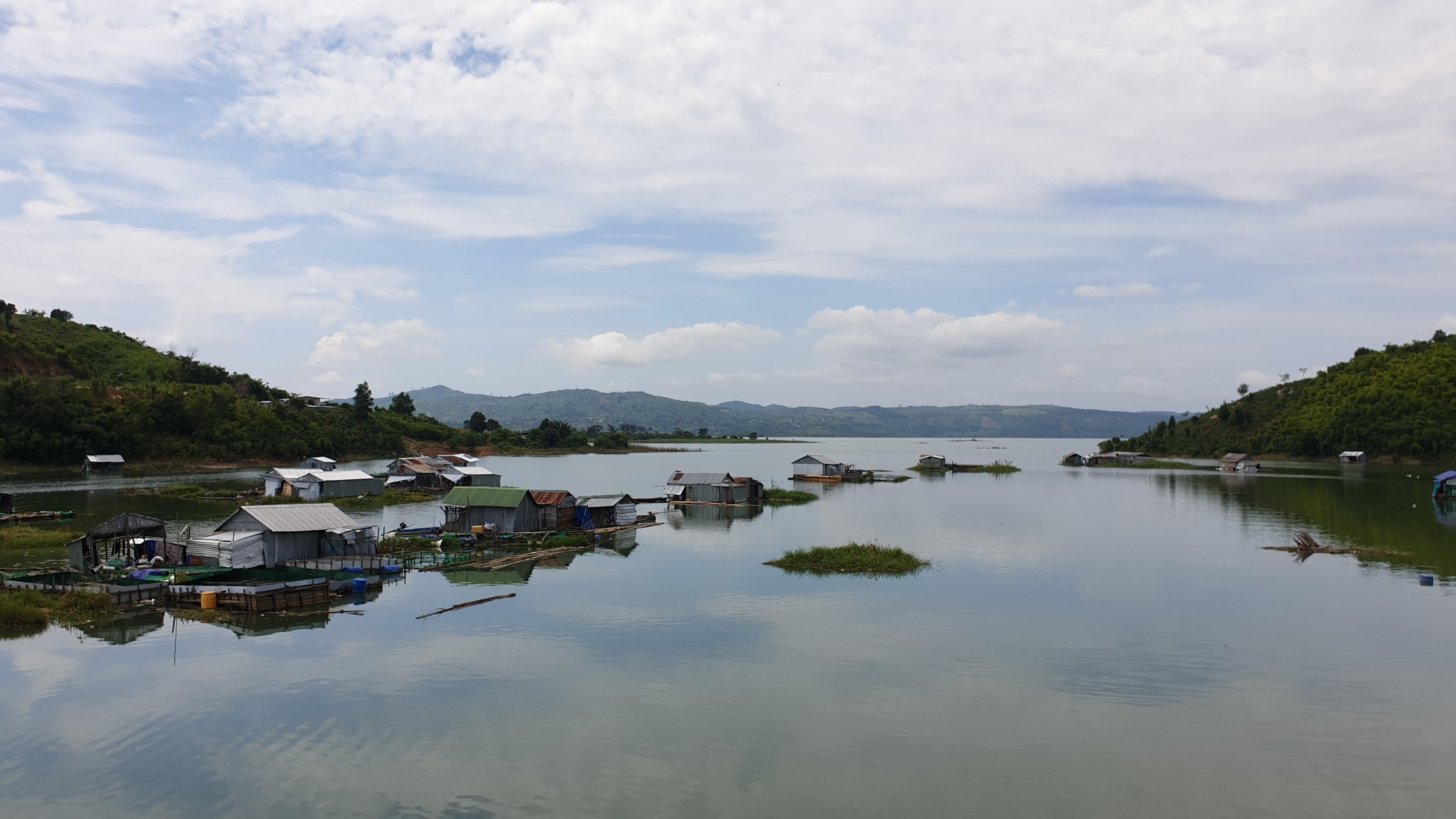 Floating village with individual homes floating on barrels in a river in rural Vietnam