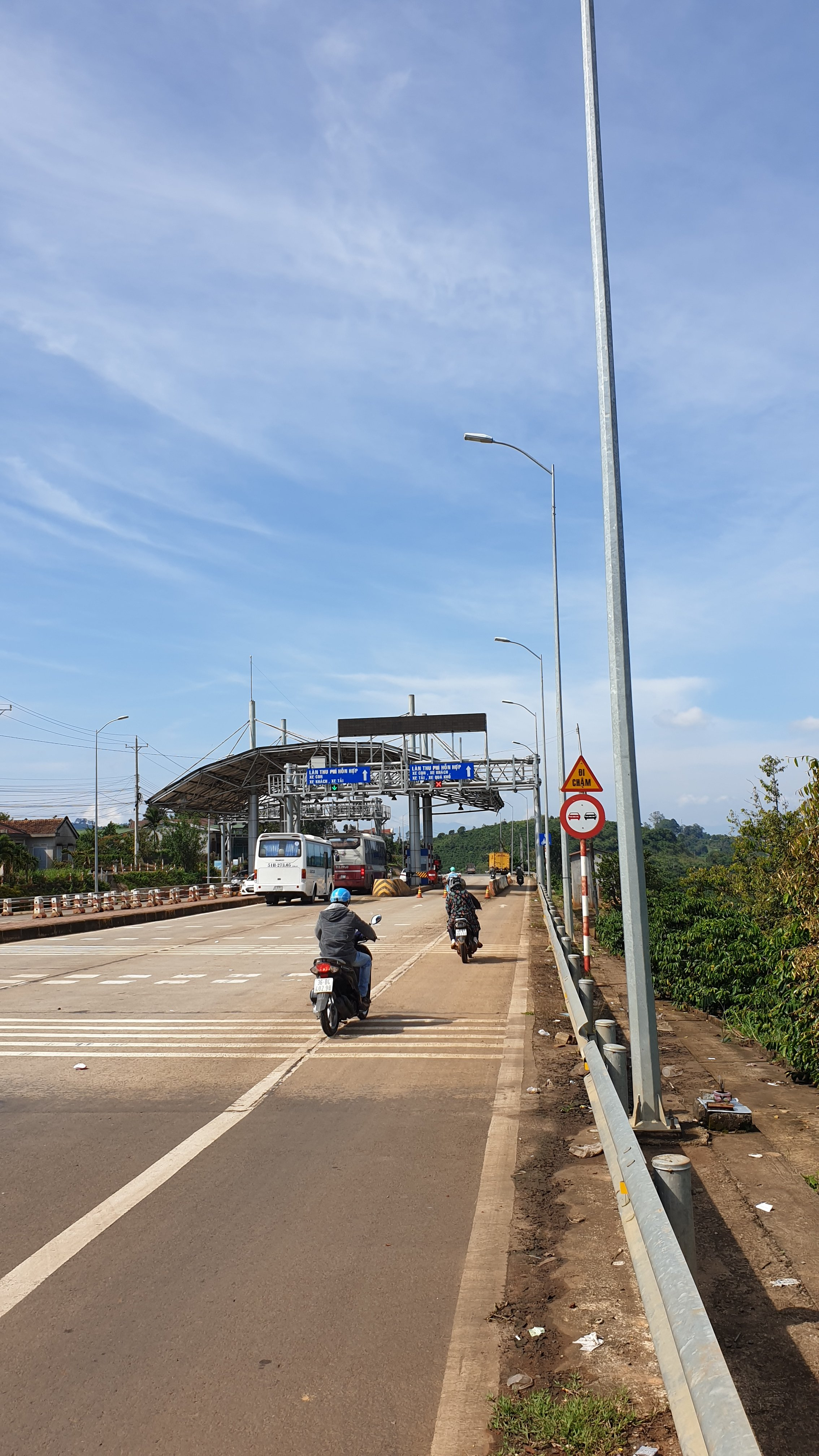 A Vietnamese toll booth with motorcycles skipping the toll through a dedicated filter lane